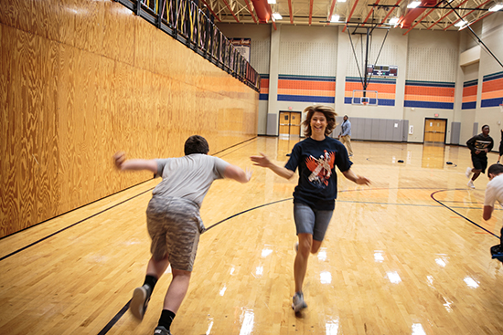 Photo of MISD School Board Secretary Stephanie O'Dell tagging off during a relay in P.E. class.