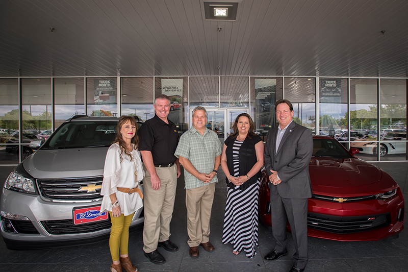 Group shot of teachers of the year in front of new cars