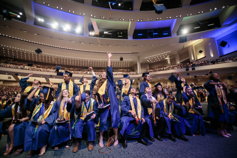 Graduates throwing caps in air