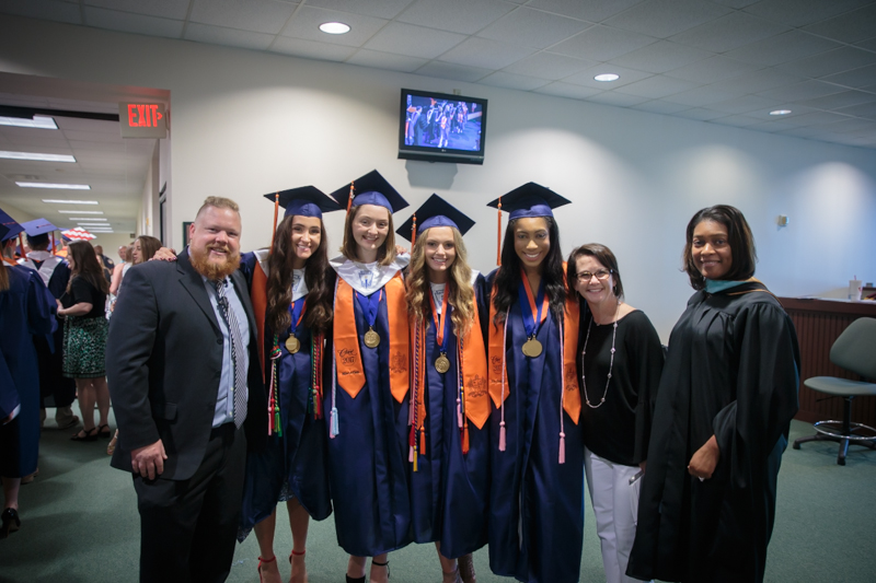Group of teachers and graduates smiling at camera