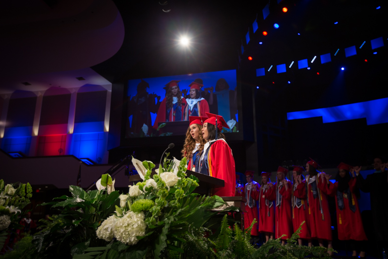 Two female graduates sing at podium