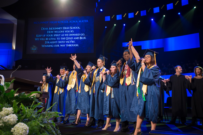 Graduates singing school song onstage