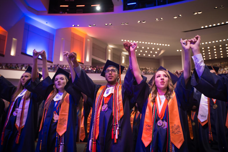 graduates holding hands singing school song