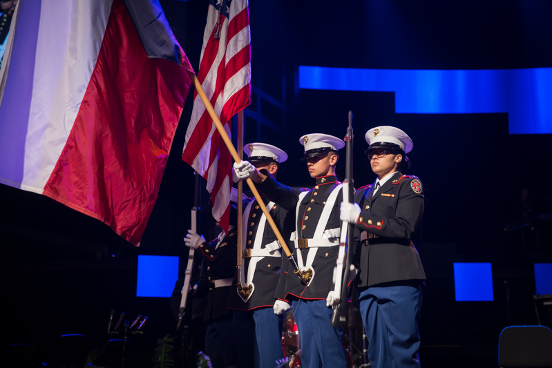 Cadets holding flags on stage