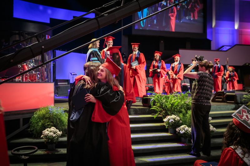 Graduate hugging after walking off stage with diploma