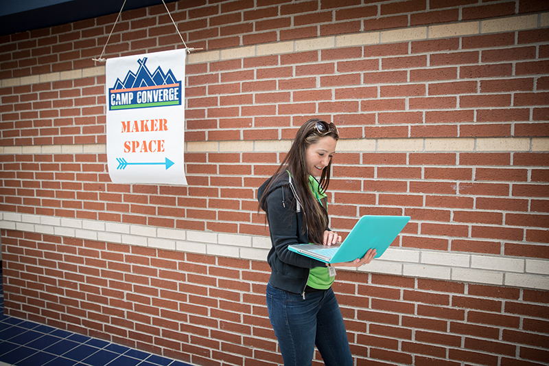 "Teacher in the hallway looking at laptop next to a Camp Converge sign that says, ""Maker Space."""