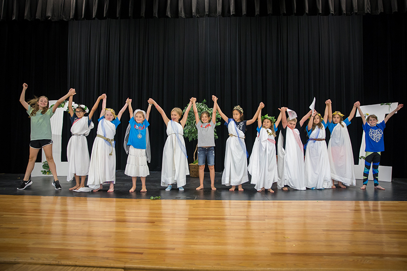 Students onstage in Greek costumes raising hands in a line.
