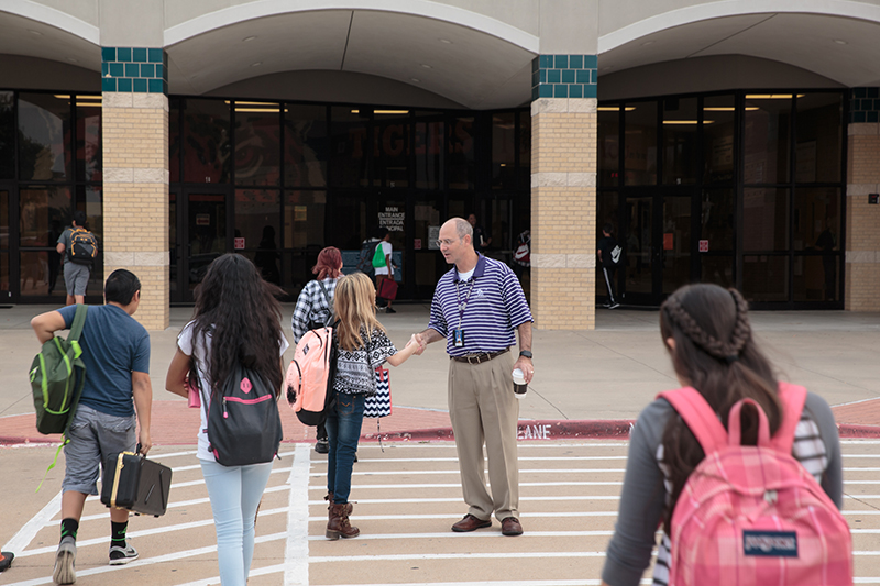 Mitch Curry shaking hands with a femail student as other students walk by in the crosswalk.
