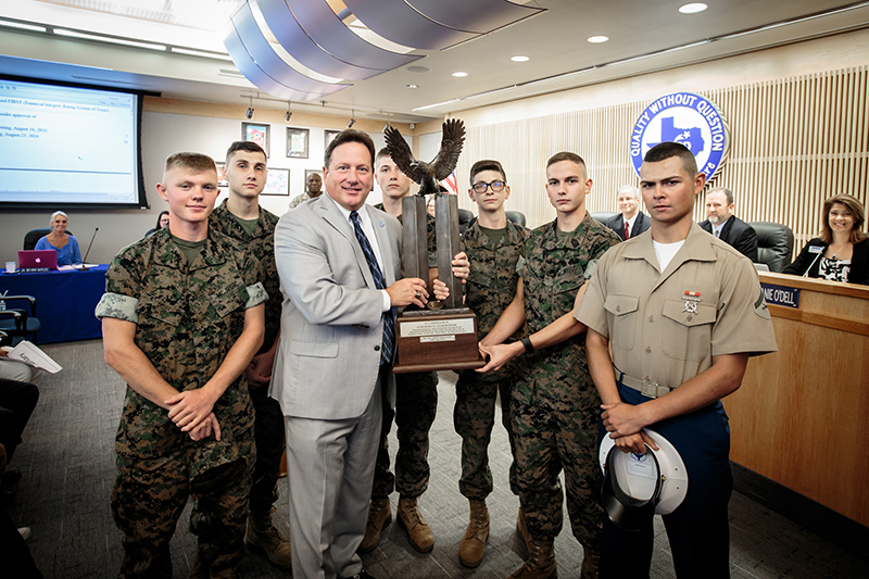 Group shot of McDaniel and cadet holding trophy surrounded by the rest of the cadet team