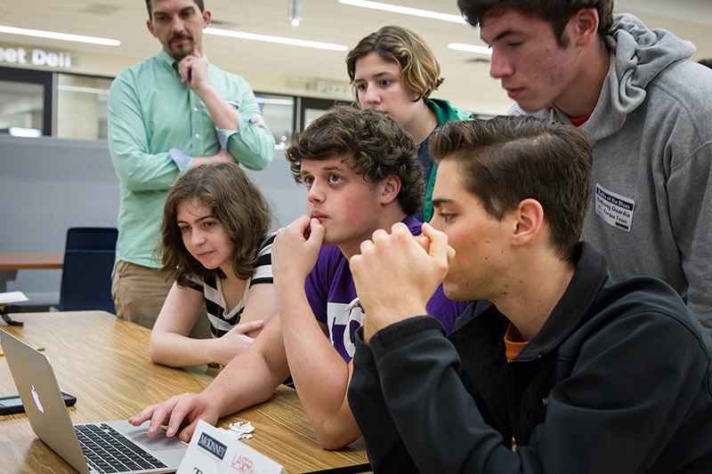 Students gathered around a computer