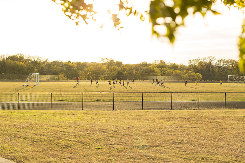 Wide view of soccer field from a distance with students playing soccer o the field