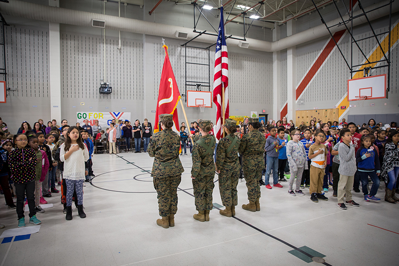 Cadets holding flags and ceremonial rifles in front of school assembly