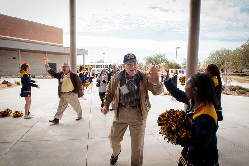 Gentleman from Senior Tour high fiving a Dowell cheerleader in front of the school