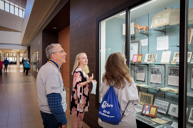 Student and two senior tour members talking in front of display case