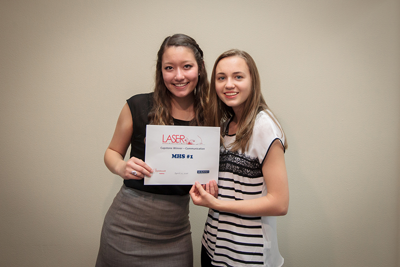 Photo of two female students holding winner certificate