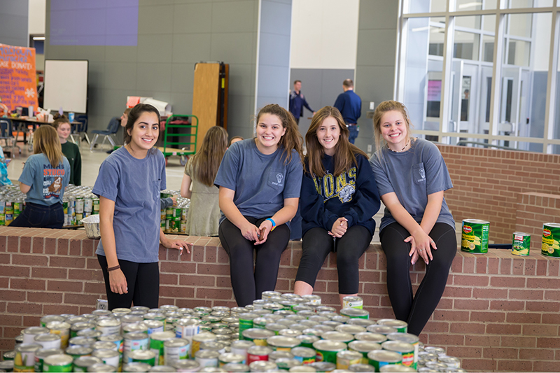 Four girls smiling by table with canned goods
