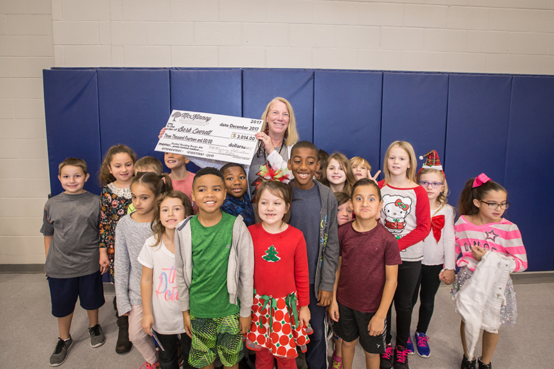 Everett holding big check in the middle of her students