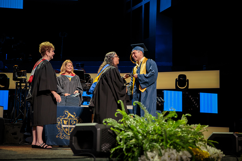 McKinzie handing graduate a diploma and shaking his hand