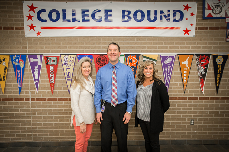 Trio in front of College Bound banner