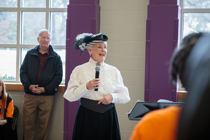Woman in historical dress talking on a microphone