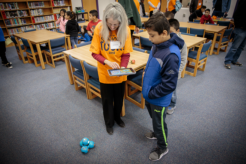 Adult holding iPad controlling robot on the floor as student looks on