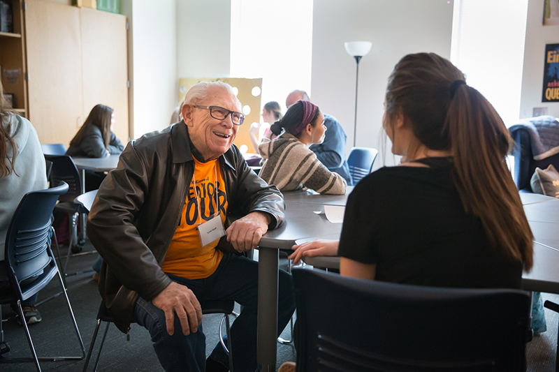 Senior adult smiling at PALS student as they talk at a table in the classroom