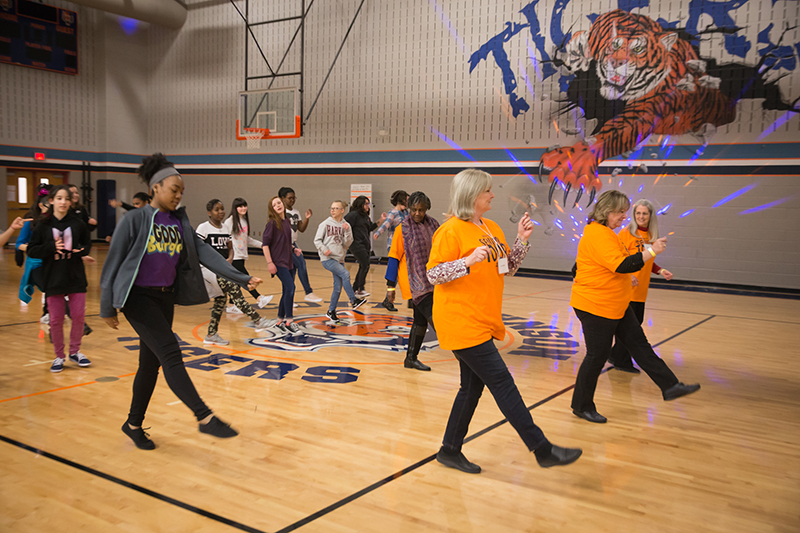 Senior Adults do dance moves in line with students dancing behind them.