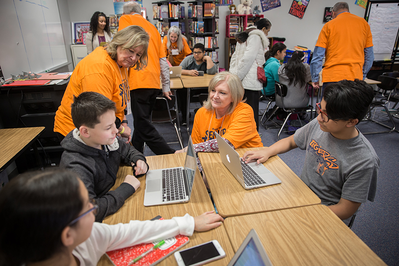 Adults talking with students working on laptops at tables