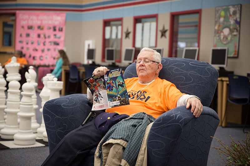 Man in chair reading a comic book