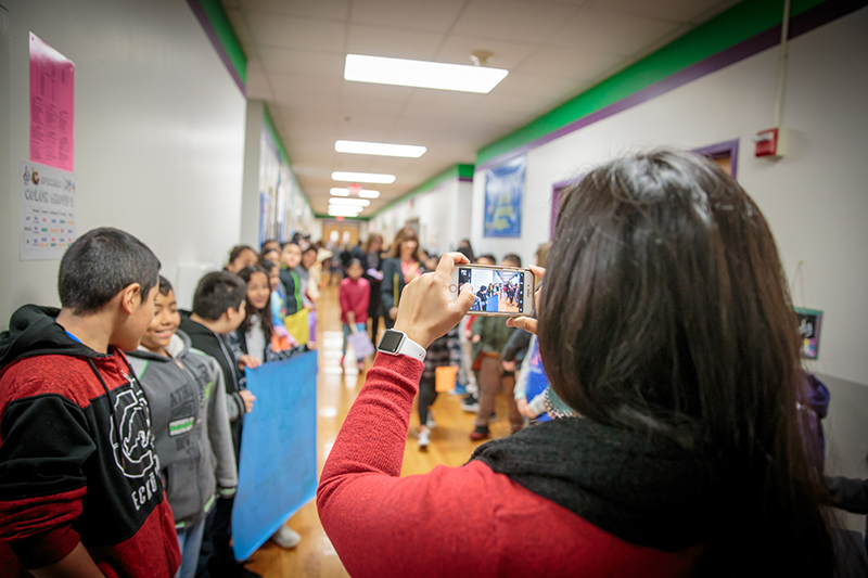 A teacher taking a picture of kids lining the hallway at Finch.