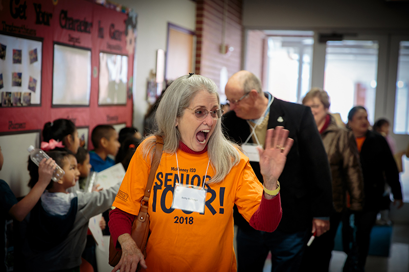 Senior Adult smiling and waving at students in the hallway at Finch