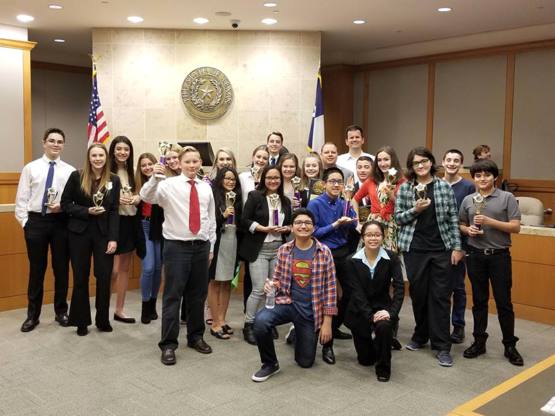 Large group of students holding up individual trophies in courtroom.