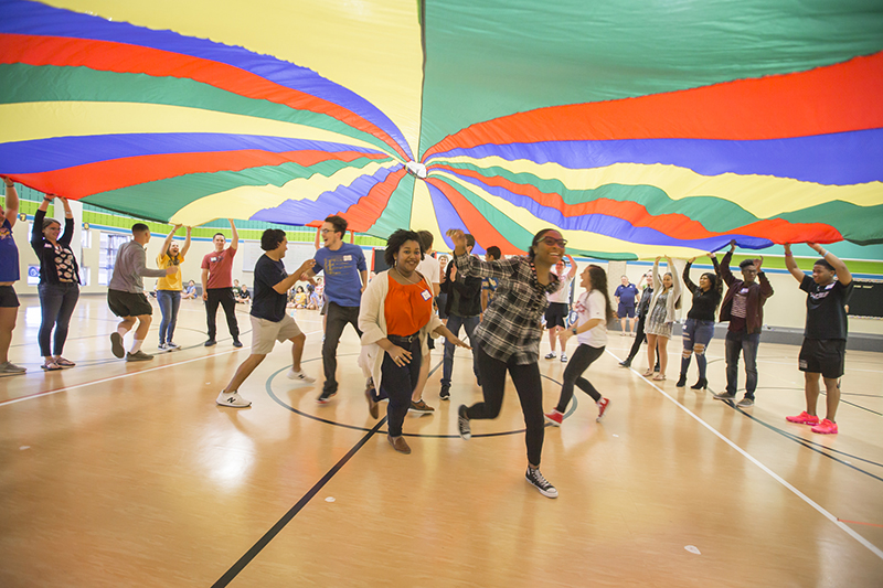 Students running to get out from under parachute