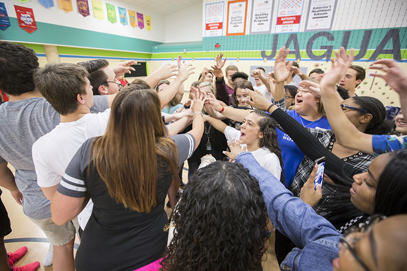 Students in a circle with hands in while shouting