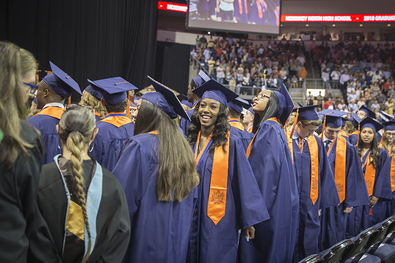 female grad smiling toward stands