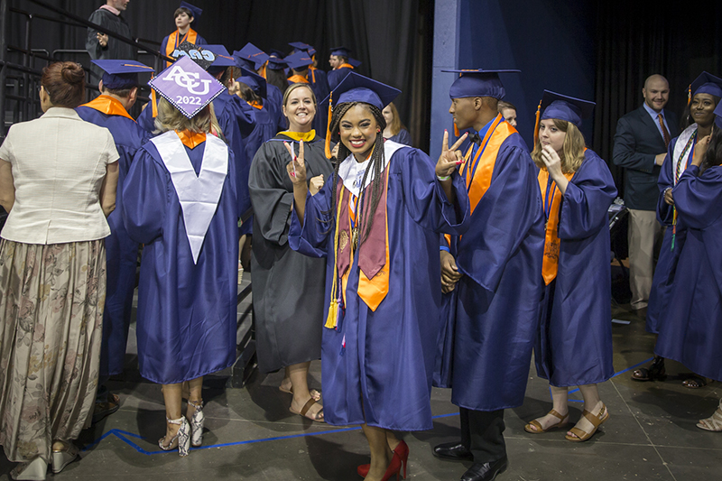 female grad showing peace sign and smiling