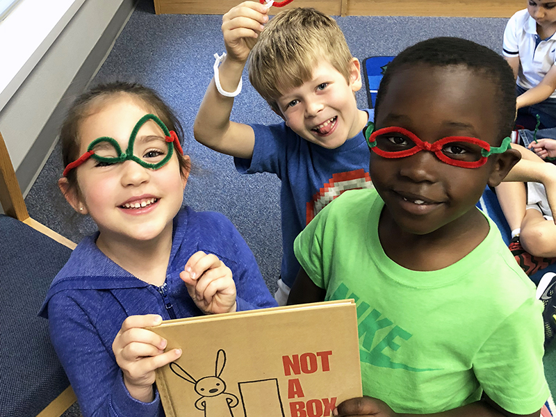 Students holding book smiling at camera with glasses they made from pipe cleaners