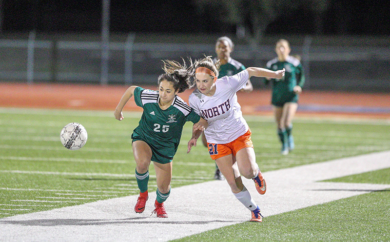 North soccer player contending for the ball during a game