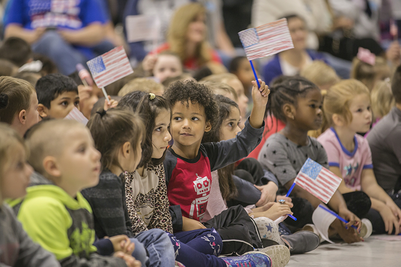 Kids sitting on floor waving flags