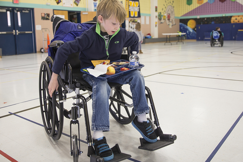 student in wheelchair with lunch tray on lap