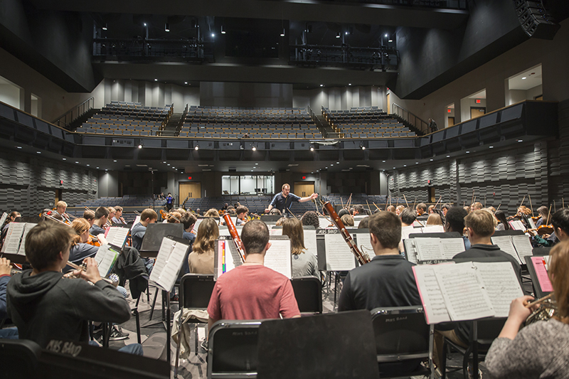 full orchestra with hall in background