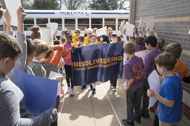 kids with banner welcoming tour