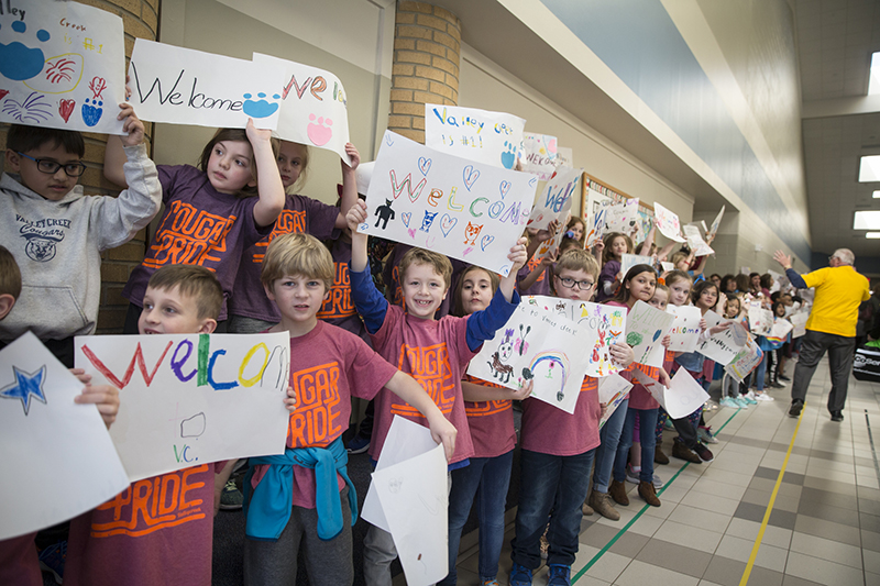 kids with welcome signs in hall