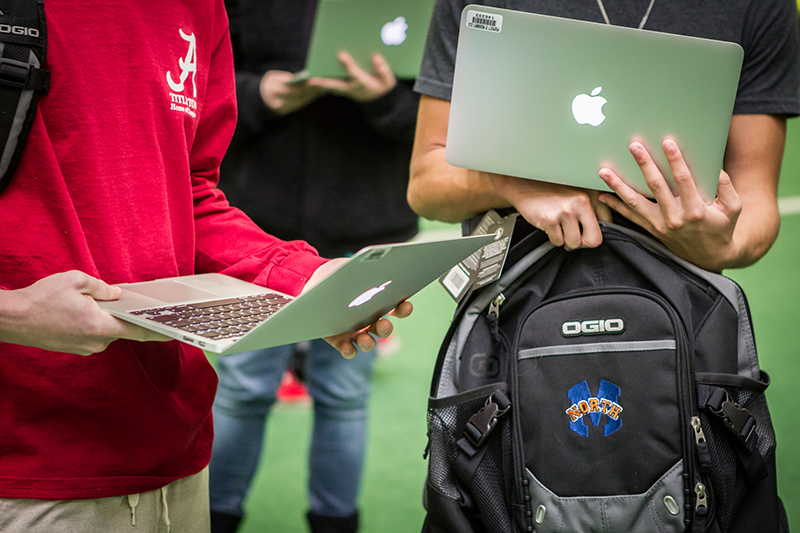 students holding laptops