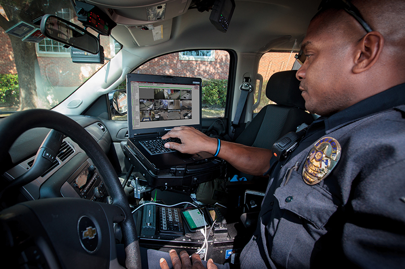 Roberts looking at computer in squad car