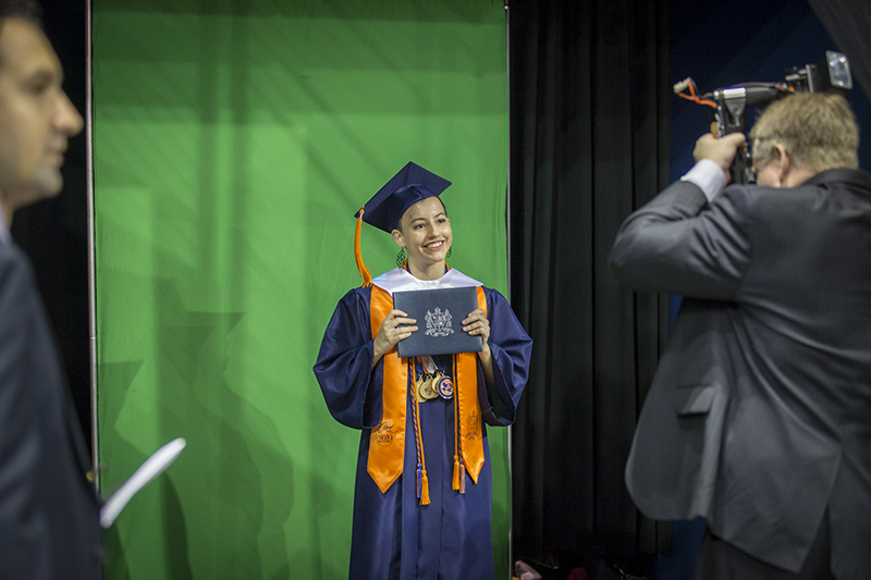 female graduate smiling with diploma in front of a green screen for photo