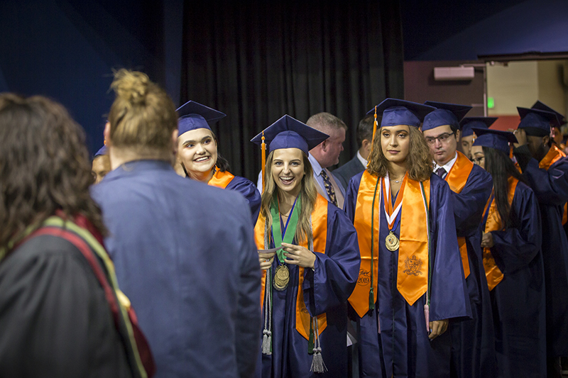 female graduates laughing as they stand in line