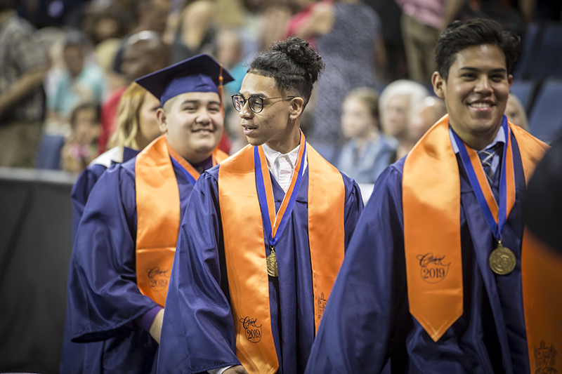 male graduates smile and walk toward exit after graduation ceremony