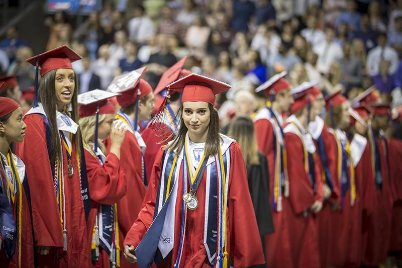 female graduate walking toward camera