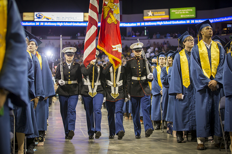 four cadets walking down center aisle in dress Marine uniforms with ceremonial rifles and flags